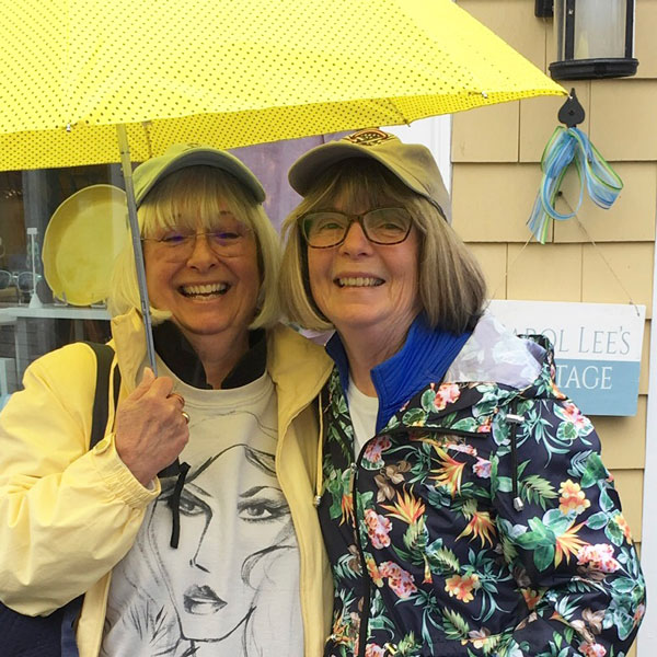 image - Carol Lee's Cottage customers. Smiling sisters in the rain, under our yellow umbrella.